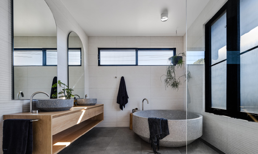 spacious bathroom featuring a large round freestanding bath in terazzo