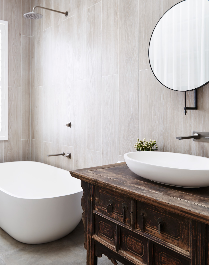 tiled bathroom featuring a stone freestanding bath and a countertop basin with a large round mirror