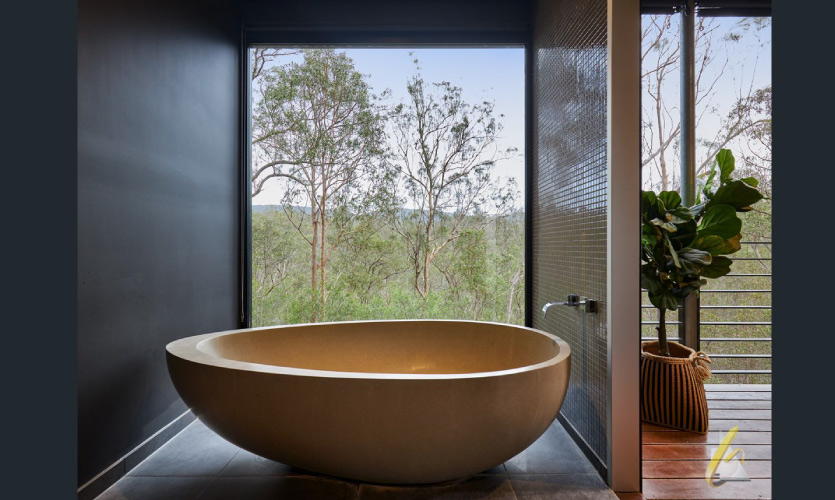 asymmetric bath placed near a large window with a view of a eucalyptus forest