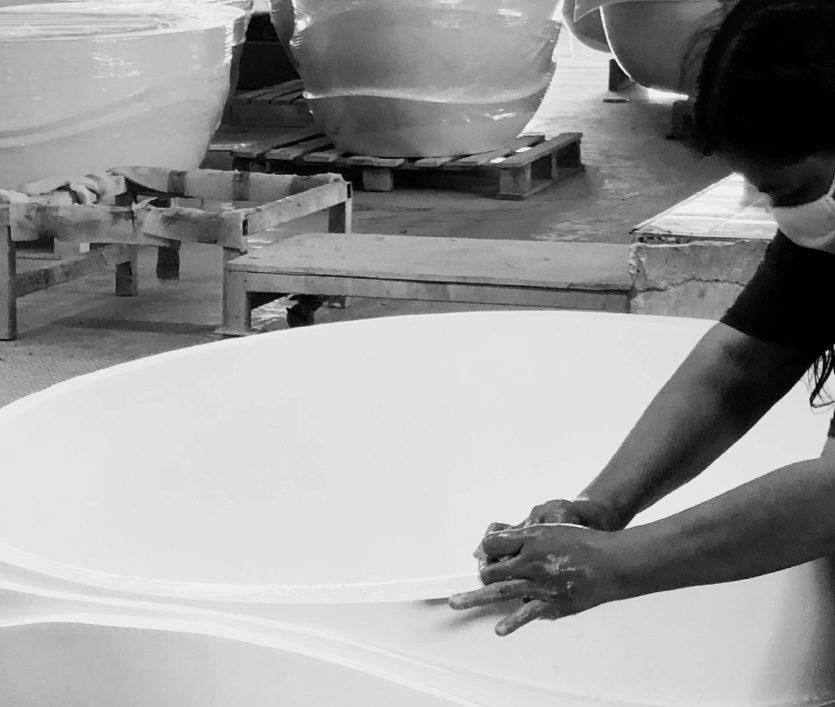 craftswoman in apaiser factory hand sanding apaiser bath